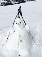 Schneemann mit Skistöcken